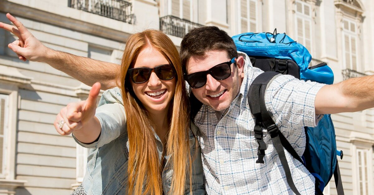 Woman with sunglasses and man with sunglasses and backpack smiling