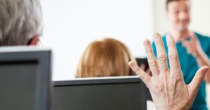 Hand raised at a desk with computers
