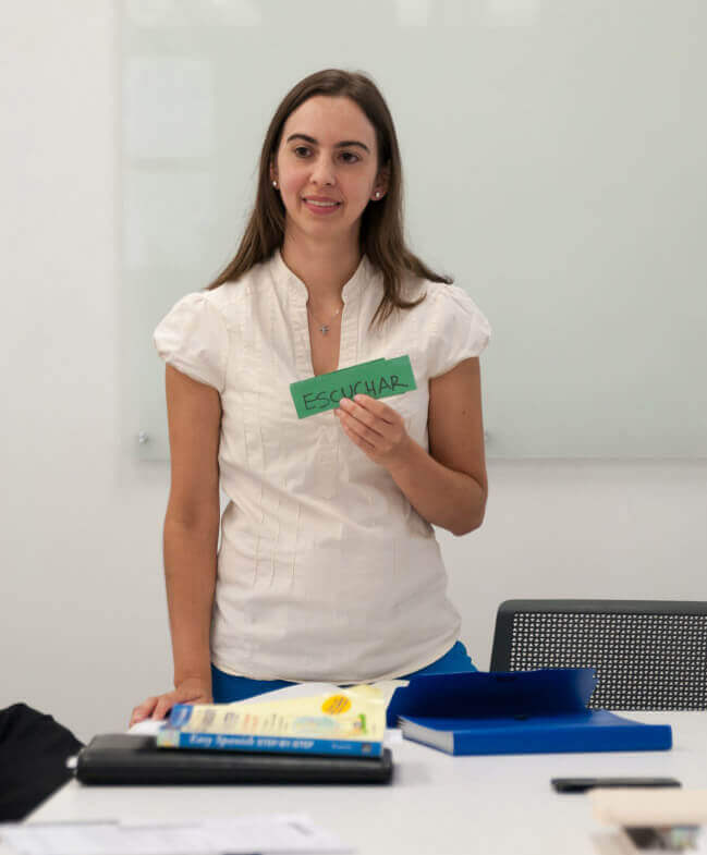 woman holding up green flashcards in class that says escuchar
