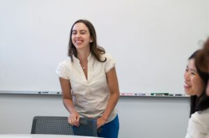 Woman teacher smiling in front of a whiteboard